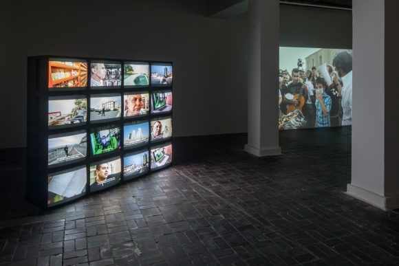 From left to right: Hiwa K, <i>The Existentialist Scene in Kurdistan (Raw Materiality 01)</i>, 2017, Multichannel video installation, <i>This Lemon tastes of Apple</i>, 2011, Single-channel HD Video, Installation view, KW Institute for Contemporary Art, Berlin 2017, Photo: Frank Sperling