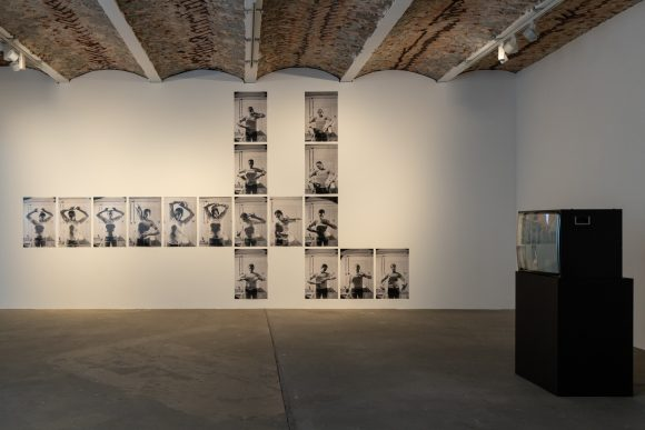 Hinten: Anna Daučíková, <i>Upbringing by Exercise</i>, 1996/2016, 17 s/w-Fotografien; vorne rechts: Anna Daučíková, We Care For Four Eyes II, 2002, HD-Video; Installationsansicht in der Ausstellung, KW Institute for Contemporary Art, Berlin, 2019, Foto: Frank Sperling