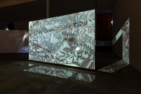 Anna Daučíková, <i>Expedition for Four Hands and Accompaniment</i> (Detail), 2019, Mixed-Media-Installation mit Dreikanal-Videoprojektion, Glas, Steine, Publikation, Installationsansicht in der Ausstellung, KW Institute for Contemporary Art, Berlin, 2019, Courtesy die Künstlerin, Foto: Frank Sperling
