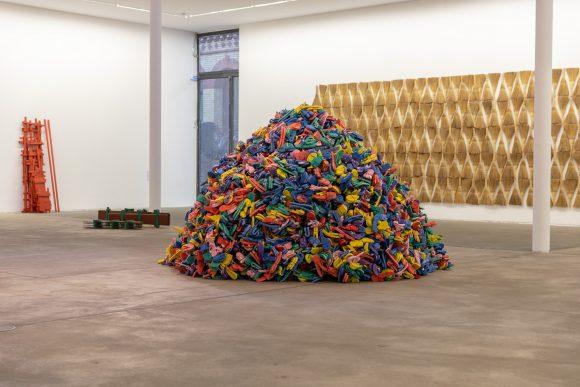 <p>Vorne mittig: Hassan Sharif, <em>Slippers and Wire</em>, 2009; hinten links: <em>Wood</em>, 2016; <em>Napoli Green</em>, 2012; hinten rechts: <em>Broom</em>, 2016; Installationsansicht der Ausstellung <em>I Am The Single Work Artist</em> in den KW Institute for Contemporary Art, 2020; Courtesy Sharjah Art Foundation Collection; Foto: Frank Sperling</p>