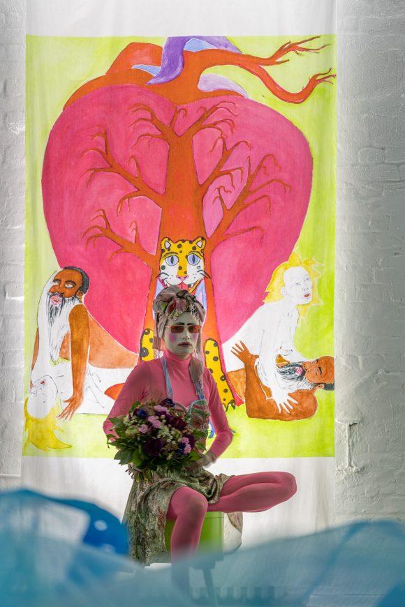 <p>Kris Lemsalu Malone, Portrait vor Kyp Malone Lemsalu <em>Love Song Sing-Along Serie 1–14</em>(Detail 10), 2019/2020; Installationsansicht in der Ausstellung <em>Love Song Sing-Along</em> in den KW Institute for Contemporary Art, Berlin 2020, Courtesy die Künstler*innen, Foto: Frank Sperling</p>