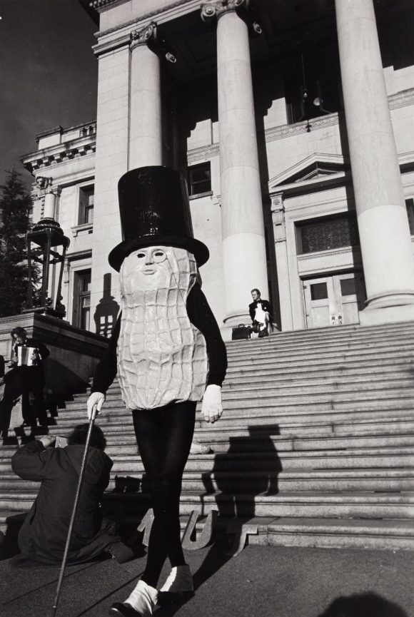 <p>Bob Strazicich, <em>Mr. Peanut Mayoral Campaign: Mr. Peanut descends steps of Vancouver Court House</em>, 1974, Silbergelatine-Druck, Sammlung des Morris/Trasov-Archivs, Morris and Helen Belkin Art Gallery, University of British Columbia</p>