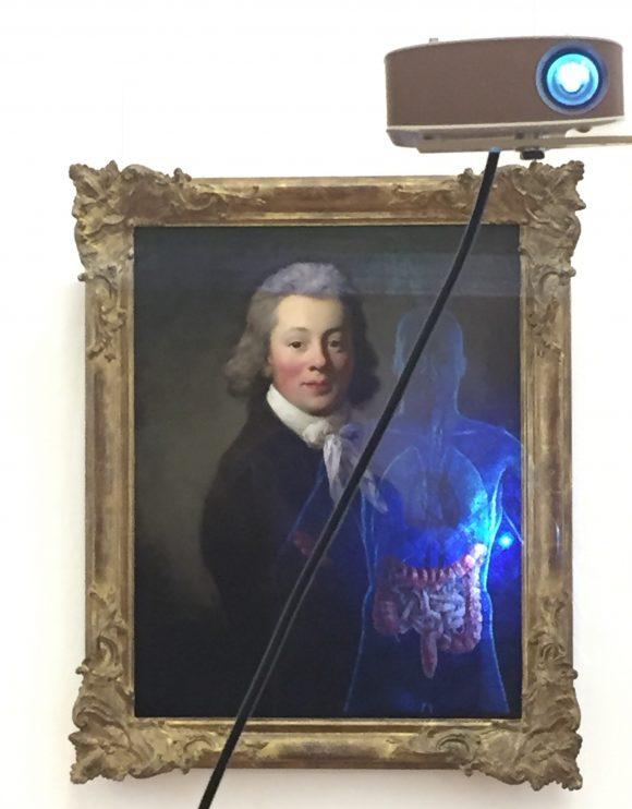 <p>Projektion auf ein Gemälde von Anton Graff, <em>Friedrich Gottlieb Benno von Heynitz</em>, 1791/92, Öl auf Leinwand, Staatliche Kunsthalle Karlsruhe, Inv. Nr. 2561; Foto: Clémentine Deliss</p>